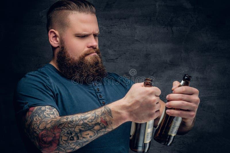 Bärtiges männliches, zwei leere Bierflaschen betrachtend stockfoto