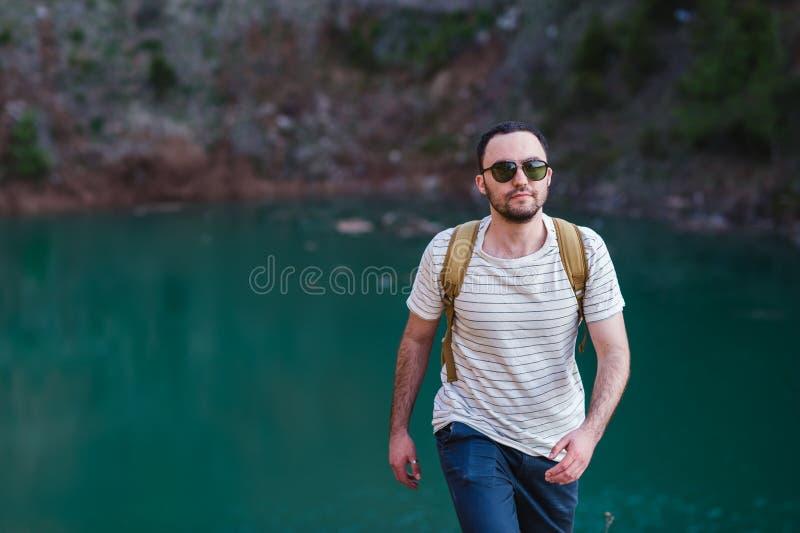 Bärtiges Mannmodell wirft neben einem grünen Wasser See auf lizenzfreie stockfotos