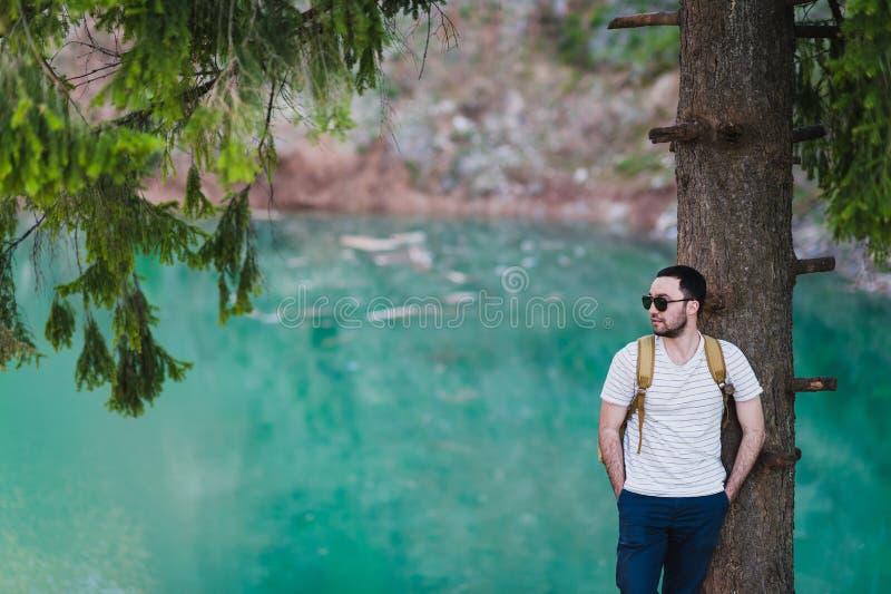 Bärtiges Mannmodell wirft neben einem grünen Wasser See auf lizenzfreies stockbild