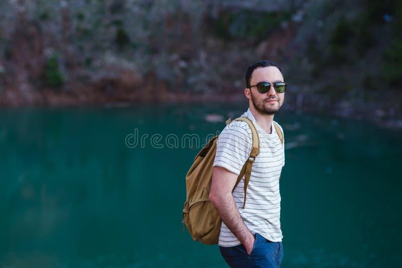 Bärtiges Mannmodell wirft neben einem grünen Wasser See auf lizenzfreie stockbilder