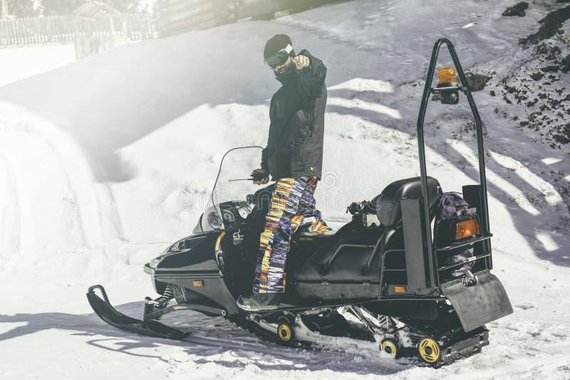 Bärtiges snowboarded Balancieren auf Schneemobil fahrung Schnee-Patrouille Unscharfer Hintergrund horizontal Optische Effekte stockfoto