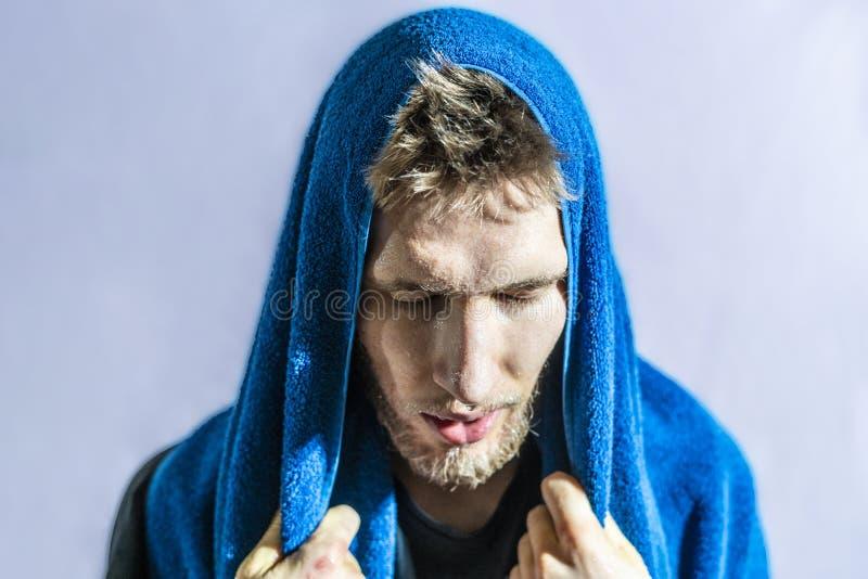 Bärtiges Sportlerabwischen weg von geschwitzten Tropfen von seinem Gesicht mit Tuch nach hartes Training lokalisiertem f lizenzfreie stockfotografie