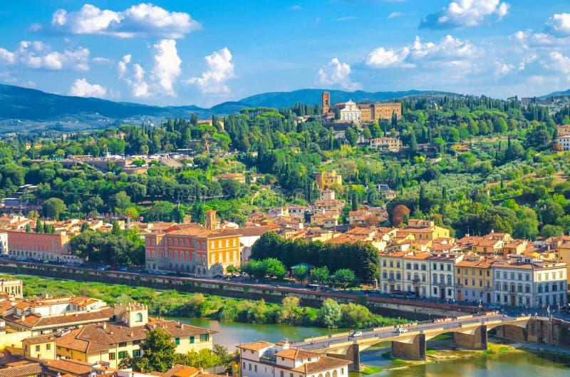 Bästa flyg- panoramautsikt av gröna kullar med Abbazia diSan Miniato al Monte, broar över den Arno floden, vita moln för blå himm royaltyfri bild