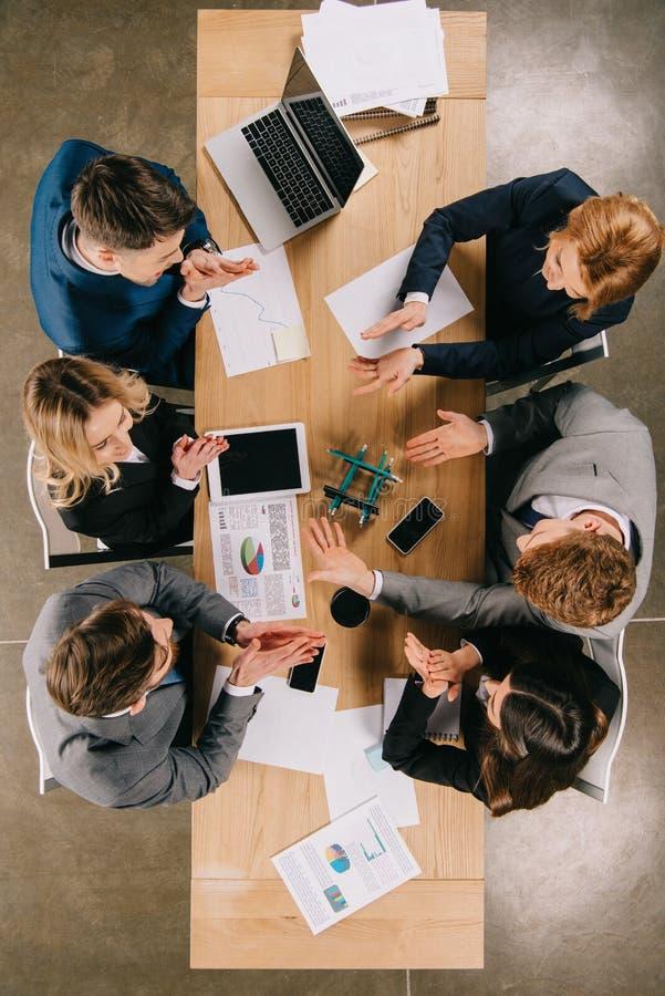 Bästa sikt av affärskollegor som gör konstruktion med blyertspennor på tabellen arkivfoto