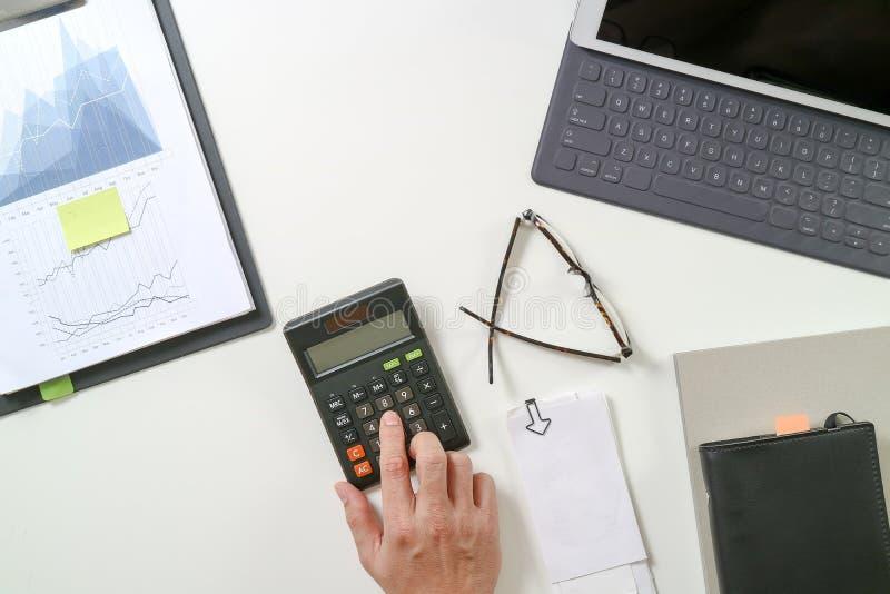 bästa sikt av affärsmanhanden som arbetar med finanser om kostnad arkivbild