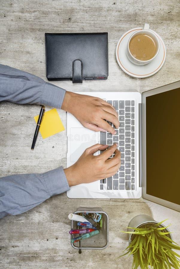 B?sta sikt av aff?rsmannen som arbetar genom att anv?nda b?rbara datorn med kaffe, den inlagda v?xten, anteckningsboken, anm?rkni royaltyfri fotografi