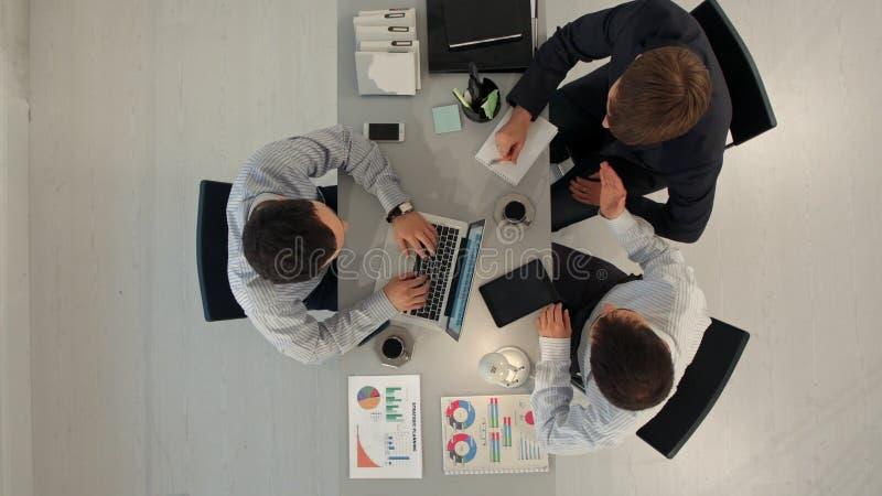 Bästa sikt av affärspartners som diskuterar dokument och idéer på mötet arkivbild
