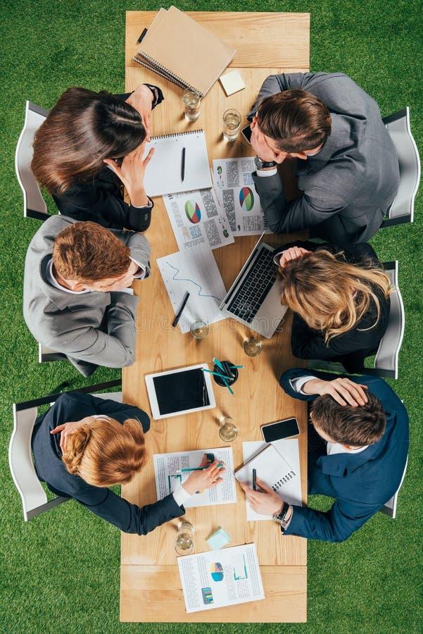 Bästa sikt av affärspartners som har diskussion på tabellen med dokument och apparater arkivfoton