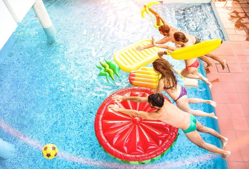 Bästa sikt av aktiva vänner som hoppar på simbassängpartiet - Vaca royaltyfri fotografi