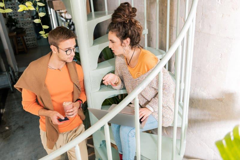 Bästa sikt av arbetsamma moderna par som tillsammans arbetar i deras kafeteria arkivbild