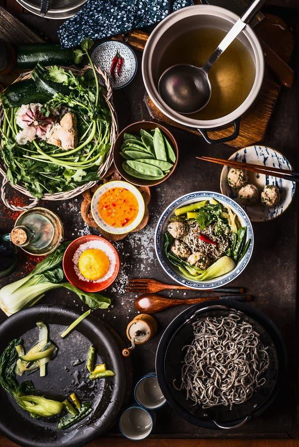 Bästa sikt av asiatisk matdisk Asiatisk förberedelse för nudelsoppa på det mörka lantliga köksbordet Kruka med materielet, lagade royaltyfri foto