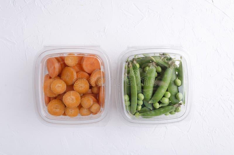 Bästa sikt av askar med nya högg av morötter och gröna nya ärtor Begrepp av sunt ?ta arkivfoto