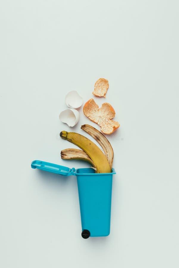 bästa sikt av avfallfacket med matavfalls som isoleras på grå färger som återanvänder begrepp arkivfoton