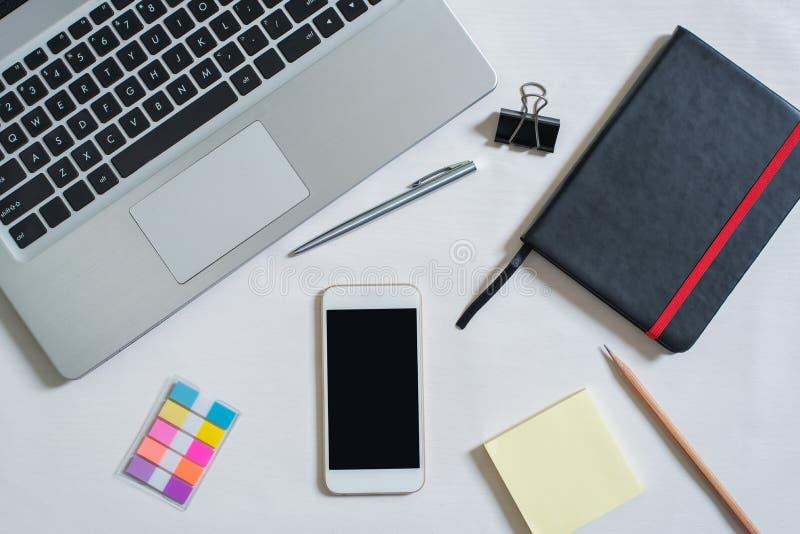 B?sta sikt av b?rbara datorn, svart anteckningsbok, mini- f?rgrik pappers- anm?rkning, mobiltelefon, penna, blyertspenna royaltyfri foto