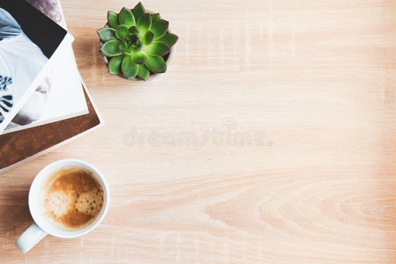 Bästa sikt av böcker och tidskrifter, kopp kaffe och suckulenta växter över träbakgrund kopiera avst?nd Begrepp av fritids- arkivfoton
