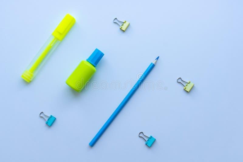 Bästa sikt av blandad brevpapper i gula och blåa färger: gem-, för korrigeringsvätska, blyertspenna- och markörpenna på vit bakgr arkivfoton