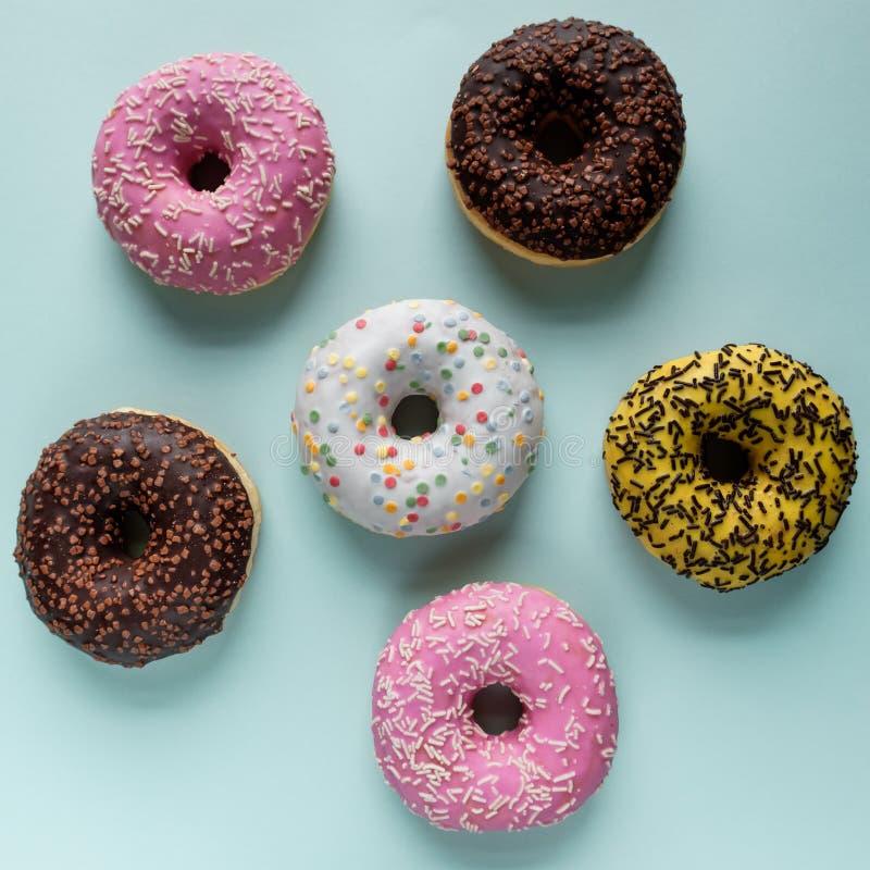 Bästa sikt av blandade donuts med frostat rosa glasat för choklad och stänk på en blå bakgrund royaltyfri foto