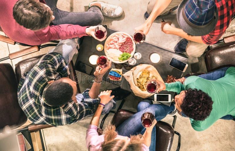 Bästa sikt av blandras- vänner som smakar rött vin på stångvinodlingen arkivbilder