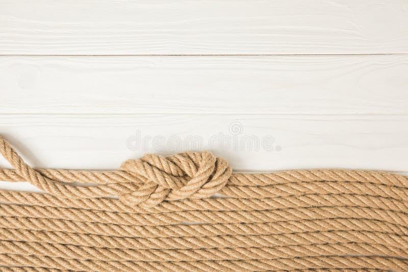 bästa sikt av bruna nautiska rep som förläggas i rad på vitt trä fotografering för bildbyråer