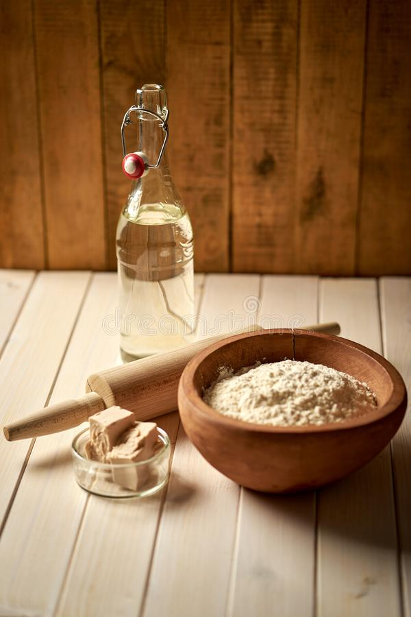 Bästa sikt av bunken av mjöl med jäst och kavlen på det vita köksbordet royaltyfri fotografi