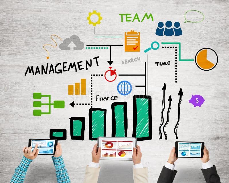 Bästa sikt av businesspeople som sitter på tabellen och använder grejer arkivbilder