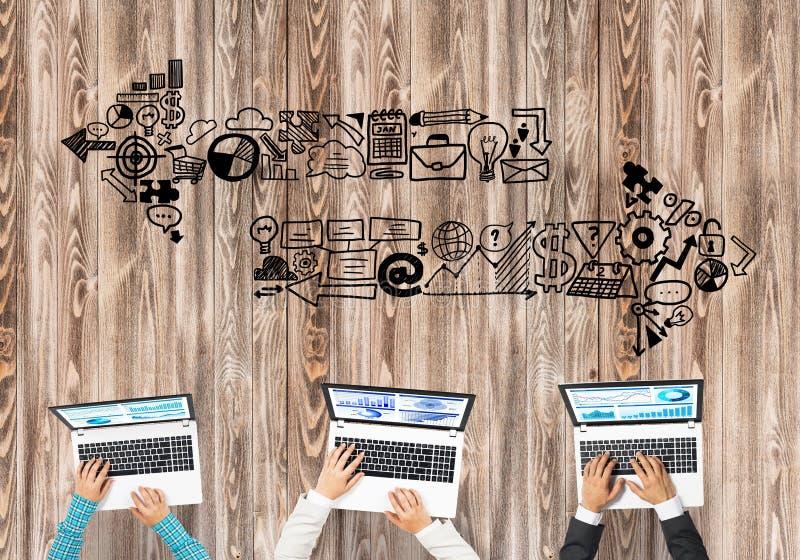 Bästa sikt av businesspeople som sitter på tabellen och använder grejer arkivfoton