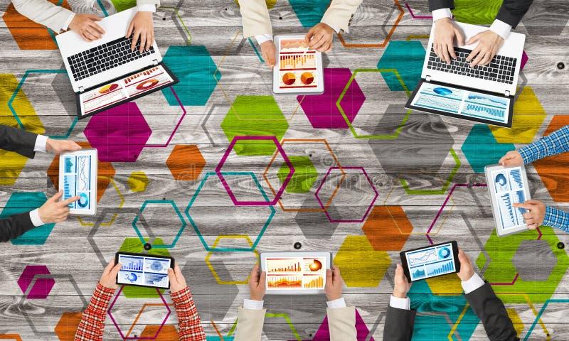 Bästa sikt av businesspeople som sitter på tabellen och använder grejer arkivbild