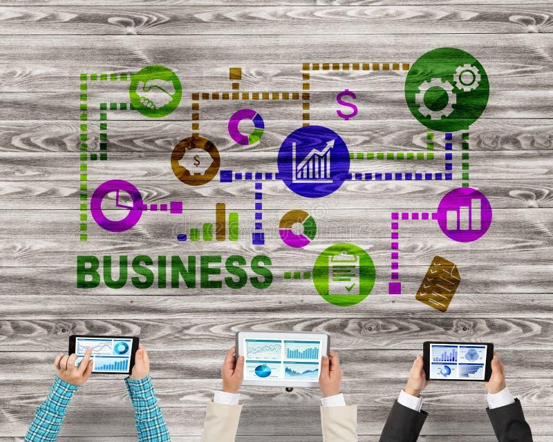 Bästa sikt av businesspeople som sitter på tabellen och använder grejer royaltyfria bilder