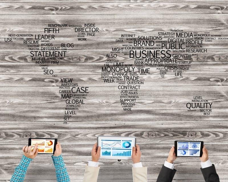 Bästa sikt av businesspeople som sitter på tabellen och använder grejer arkivfoto