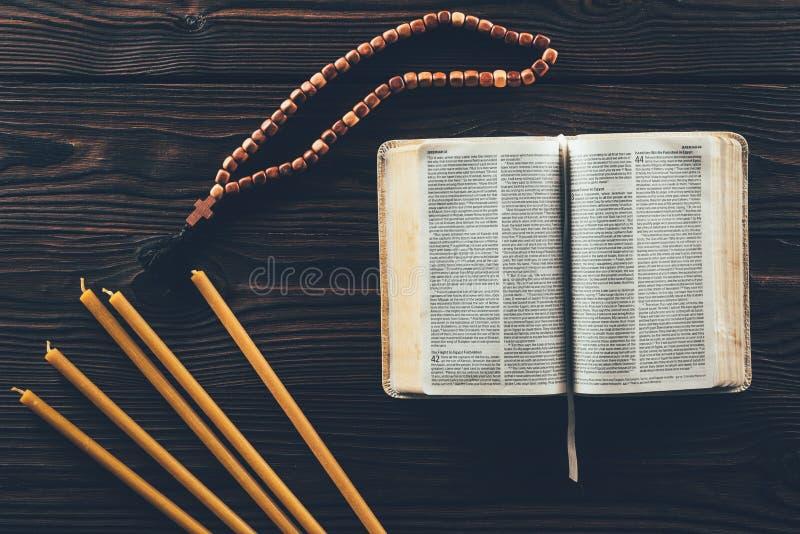 bästa sikt av den öppna heliga bibeln med radbandet och stearinljus arkivfoto