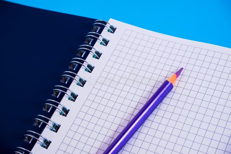 Bästa sikt av den öppna spiral tomma anteckningsboken med blyertspennan på blå skrivbordbakgrund royaltyfri bild