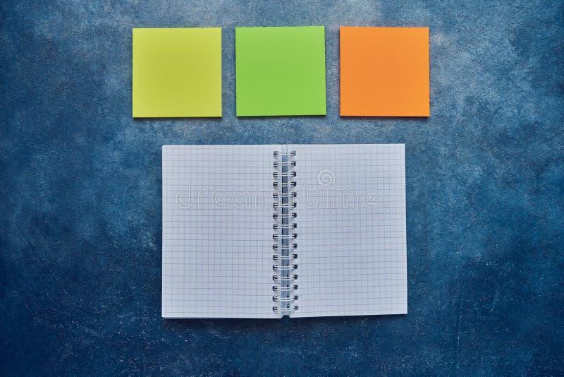 Bästa sikt av den öppna spiral tomma anteckningsboken och tom anmärkningsklistermärke på en blå bakgrund tillbaka begreppsskola t royaltyfria bilder