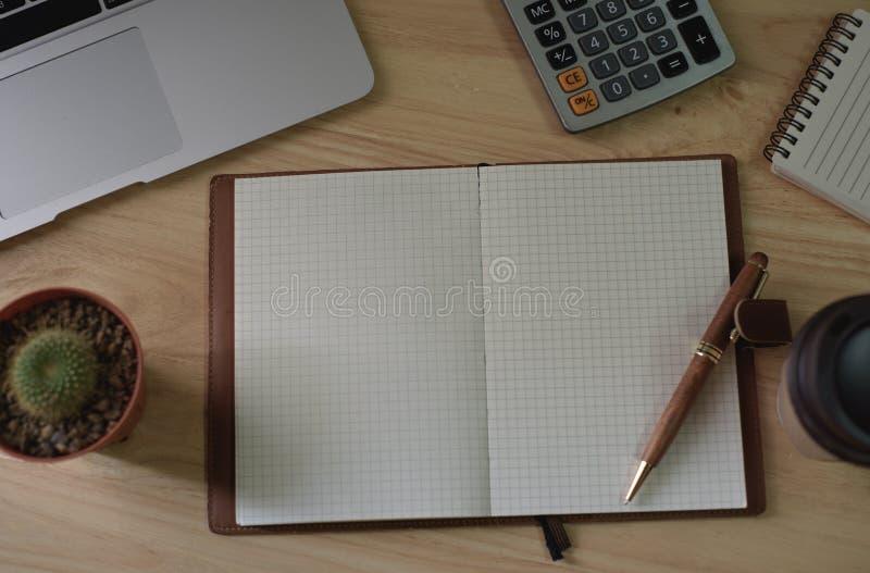 Bästa sikt av den anmärkningsboken och pennan med bärbara datorn på den wood tabellen royaltyfria foton