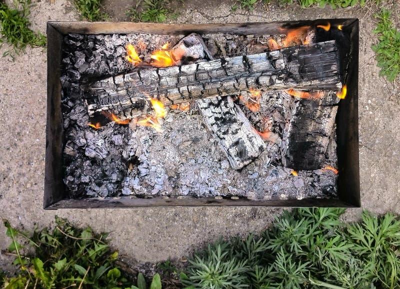 Bästa sikt av den campa bärbara kolgrillfesten för A med brandflammor, grönt gräs omkring royaltyfri bild
