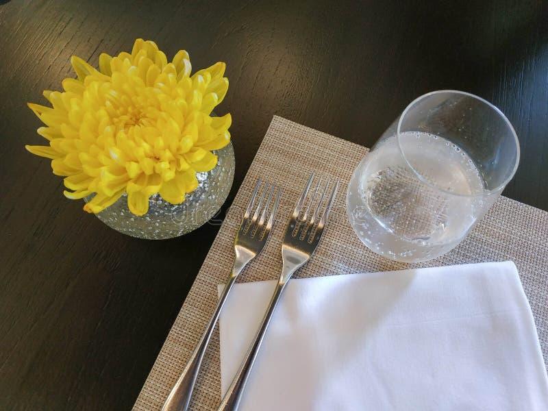 Bästa sikt av den dekorerade tabellen med crystal exponeringsglas, linneservetten, gafflar och den gula blomman arkivbild