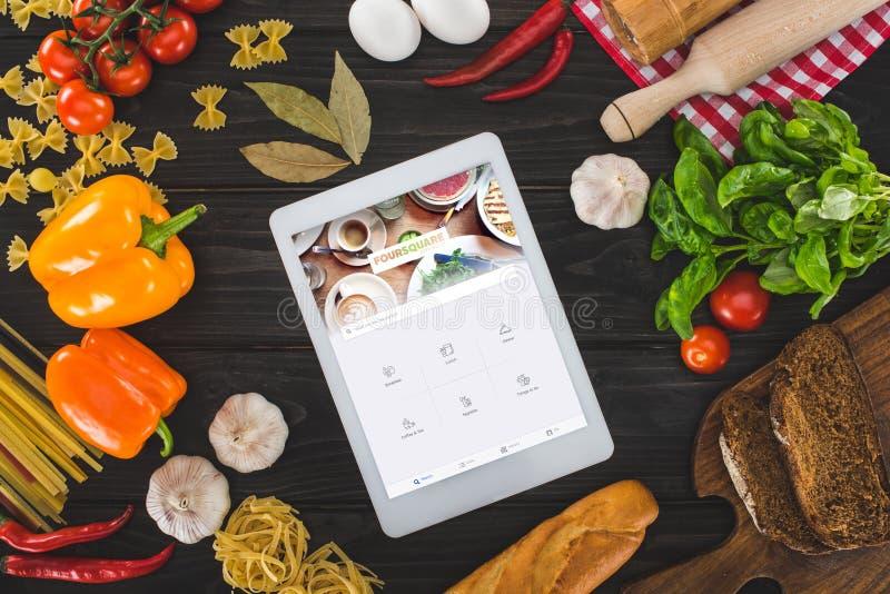 bästa sikt av den digitala minnestavlan med foursquare websiten och nya ingredienser royaltyfri bild