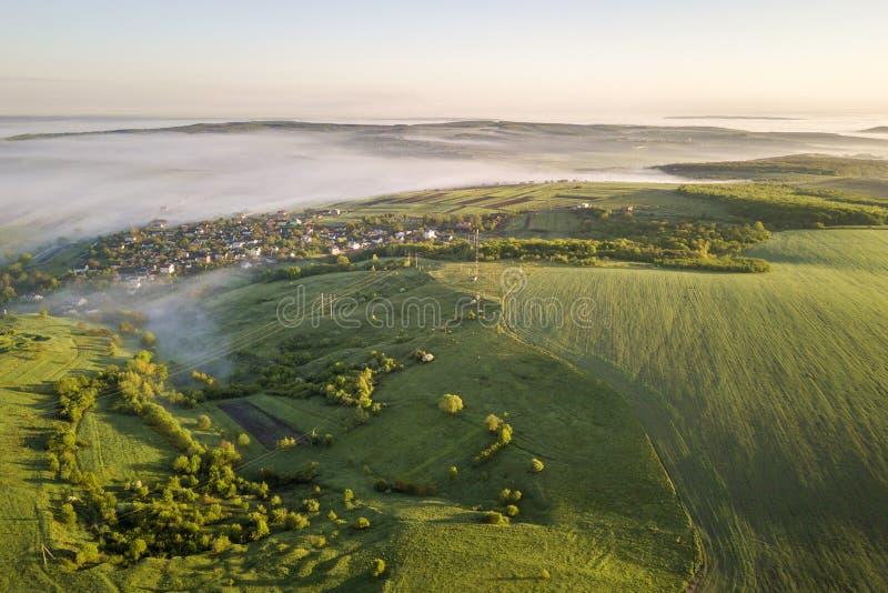 Bästa sikt av den dimmiga gröna gräs- kullen, byhustak i dalen bland gröna träd på bakgrund för blå himmel Dimmig vår arkivbilder