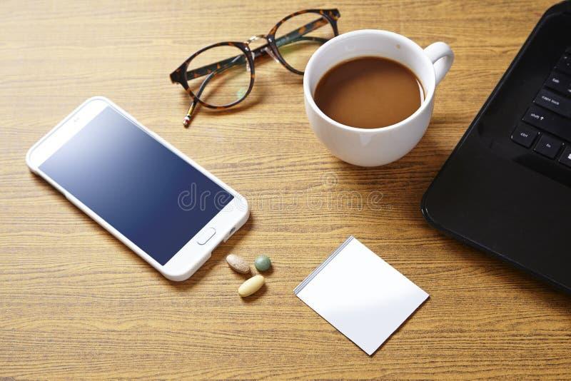 Bästa sikt av den funktionsdugliga tabellen med den kopp kaffe-, medicin- och bärbar datordatoren arkivbilder