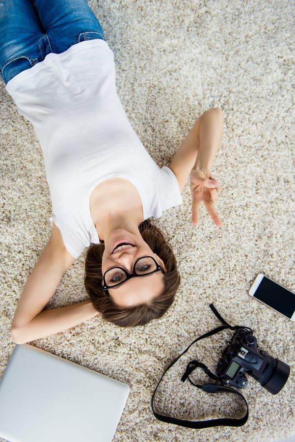 Bästa sikt av den gladlynta lyckliga kvinnan som ligger på golv med kameran, gla royaltyfri foto