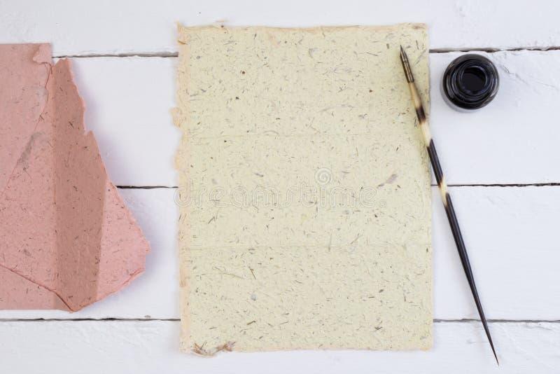 Bästa sikt av den gulingpapper, fjäderpennan och färgpulver på den vita däcktabellen royaltyfria foton
