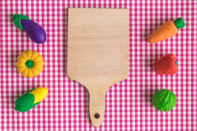 Bästa sikt av den gummigrönsakmodeller och skärbrädan på tabellabstrakt begrepp fotografering för bildbyråer