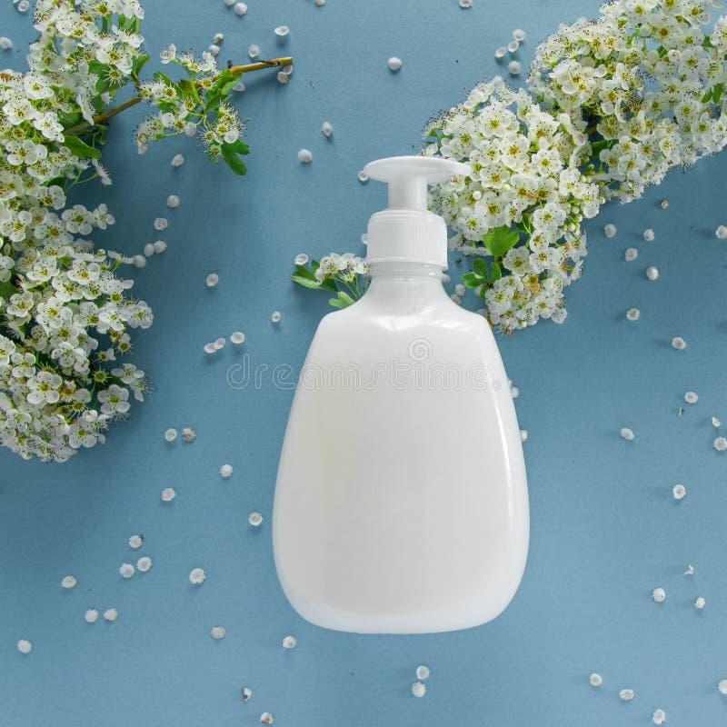 Bästa sikt av den hygieniska/kosmetiska produkten och blommor på mjuk blå bakgrund Wellnessskönhetbehandling royaltyfria bilder
