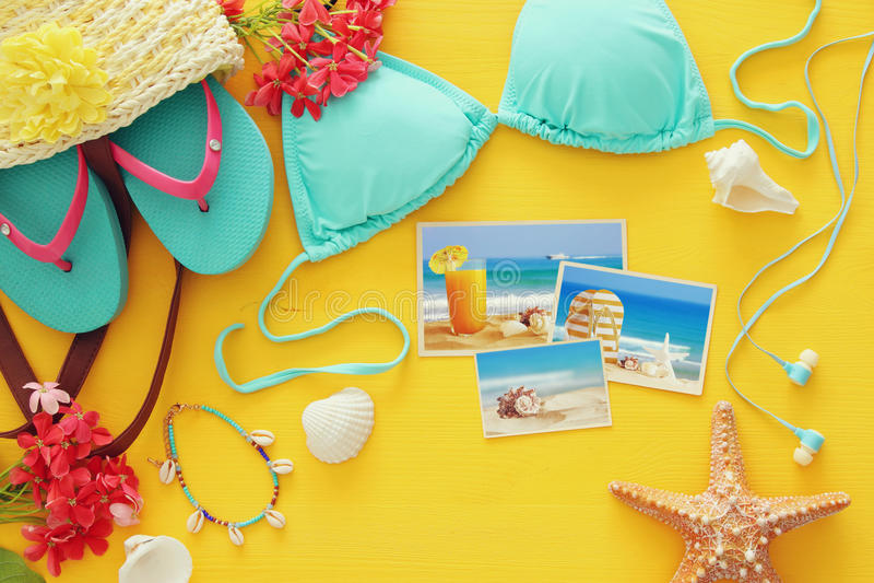 Bästa sikt av den kvinnliga baddräktbikinin för mode på gul träbakgrund Begrepp för sommarstrandsemester arkivfoton