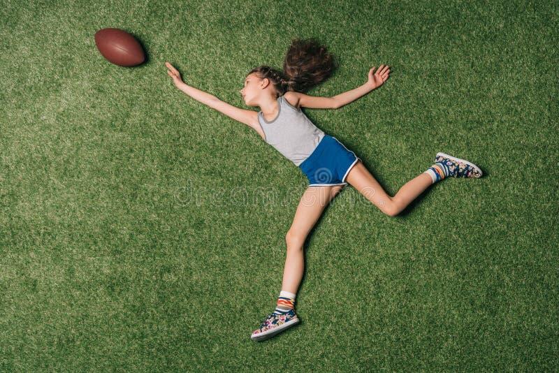 Bästa sikt av den lilla sportive flickan som fångar rugbybollen på gräs, royaltyfria bilder