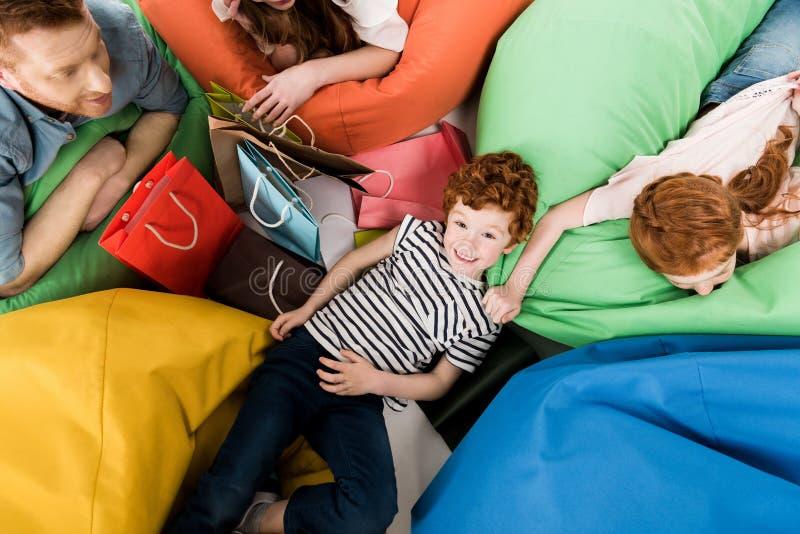 bästa sikt av den lyckliga unga familjen med shoppingpåsar som vilar på bönapåse royaltyfri fotografi