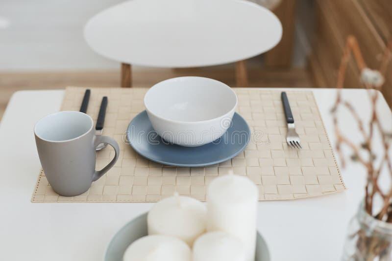 Bästa sikt av den olika dishwaren på den vita matställetabellen - keramiskt plattor, kopp, gaffel, sked och knive fotografering för bildbyråer