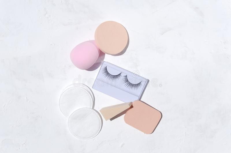 Bästa sikt av den olika kosmetiska svampen och nya falska ögonfrans i asken på den vita yttersidan royaltyfri bild