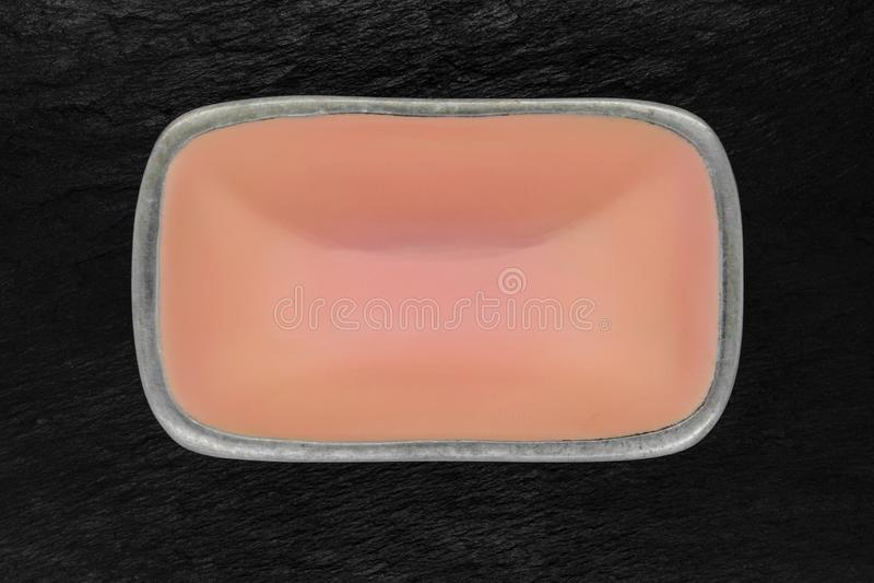 Bästa sikt av den rektangulära rosa tomma maträtten med silverkanter på svart stenbakgrund royaltyfria bilder