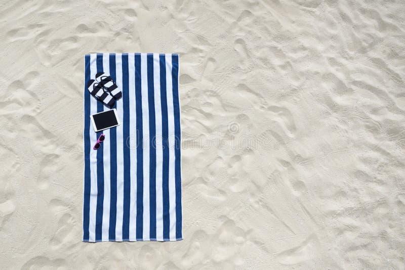 Bästa sikt av den sandiga stranden med handdukram- och sommartillbehör royaltyfria foton