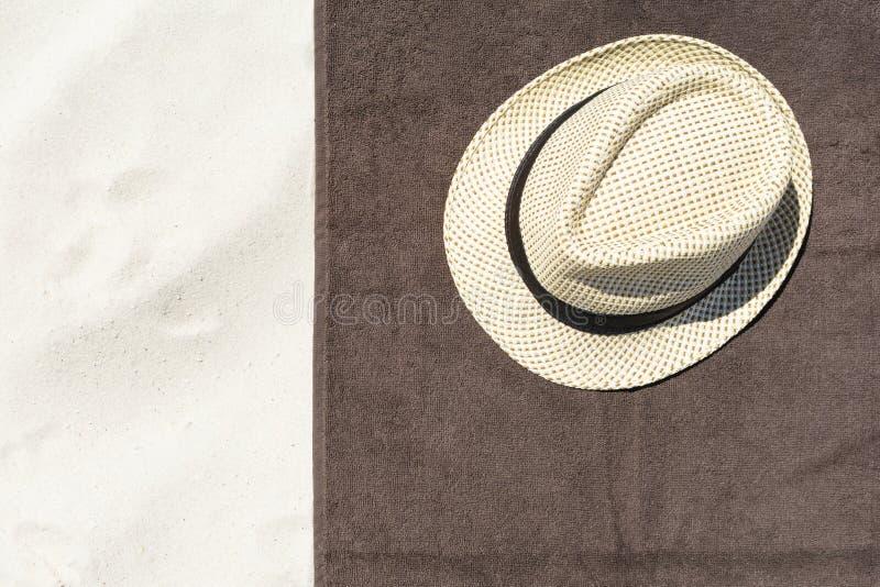 Bästa sikt av den sandiga stranden med handdukram- och sommartillbehör Bakgrund med den kopieringsutrymme, handduken och hatten royaltyfria bilder